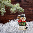Christmas decorations. Happy snowman, fir-tree, tinsel on wooden — Stock Photo
