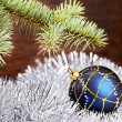 Christmas decoration. Blue ball, tinsel and fir-tree — Photo