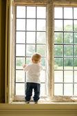 Joven mirando por la ventana — Foto de Stock