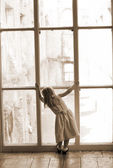 Young girl looking out a window — Stock Photo