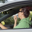 Female driver doing make-up in car — Stock Photo