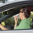 Stock Photo: Female driver doing make-up in car