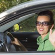 Cute woman in the car waving hello — Stock Photo