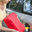 Stock Photo: Mid aged woman adding fuel in car
