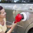 Mid aged cute woman polishing car — Stock Photo