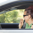 Stock Photo: Mid aged womsneeze in car