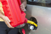 Adding fuel in car with plastic can — Stok fotoğraf