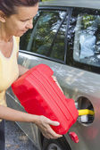 Mid aged woman adding fuel in car — Stock Photo