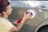 Mid aged cute woman polishing car — Stock Photo