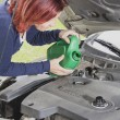 Cute woman is adding oil in the car — Stock Photo