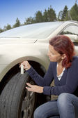 Woman driver measuring tyre profile — Stock Photo