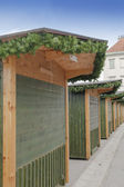 Row of wooden houses decorated with fresh pine Christmas garlands, before opening of the Christmas fair — Stock Photo