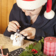Cute girl making cotton-wool snowman — Stock Photo