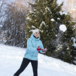 Smiling girl catching snowball — Stock Photo
