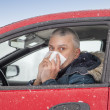 Mid aged man sneezes in a car — Stock Photo