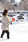 Mid aged woman with candle on snowy cemetery — Stock Photo