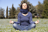 Mid aged woman doing yoga exercises outside — Stock Photo