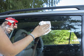 Cleaning car window on sunny morning — Stock Photo