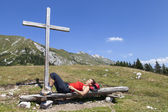 Woman resting under wooden cross — Stock Photo