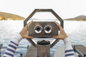 Looking through coin operated binoculars — Stockfoto