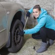 Changing tires, Young woman loosening nuts on a car wheel — Stok fotoğraf