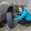 Young woman driver changes car tyres — Stok fotoğraf #35327795