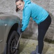 Changing tires, Young woman loosening nuts on a car wheel  — Stock fotografie