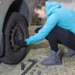 Young woman driver changes car tyres — Stock Photo