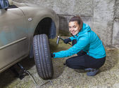 Young woman driver changes car tyres — Stok fotoğraf
