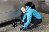 Young woman driver changes car tyres — 图库照片