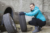 Young smiling woman driver replacing tires — Foto Stock