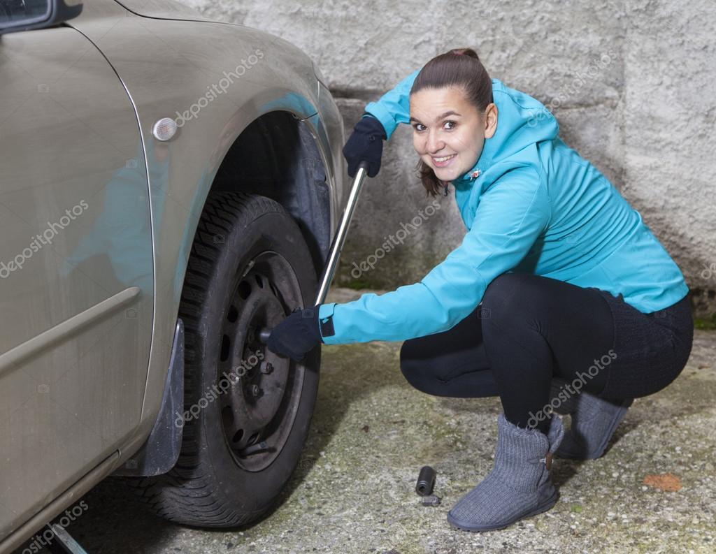 changer les pneus noix desserrage de la jeune femme sur une roue de voiture photographie. Black Bedroom Furniture Sets. Home Design Ideas