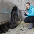 Young smiling woman driver replacing tires, showing OK sign — Stock Photo