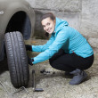 Pretty girl replacing car tyre — Stock Photo #36121811