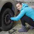 Pretty girl replacing car tyre — Photo