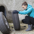 Pretty girl replacing car tyre — Stockfoto