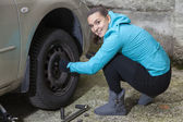 Pretty girl replacing car tyre — Stock Photo
