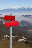 Red mountain guidepost along an alpine pathway — Stock Photo