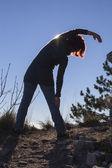 Silhouet van een vrouw uitvoeren van yoga met de zon achter haar — Stockfoto