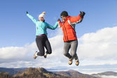 Two happy women joyfully jumping outdoors — Stock Photo