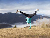 Young women performing one handed cartwheel — Stock Photo