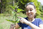 Girl touching stinging nettle leaves — Stock Photo