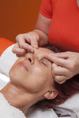 Милая женщина получает профессиональный массаж лица, лимфодренаж — Стоковое фото