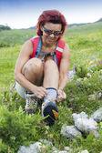 Woman hiker tying the shoelaces — Stok fotoğraf