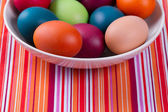Colorful hand dyed easter eggs in a bowl on a table with striped — Stock Photo