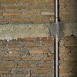 Brick wall with metal pipe. — Stock Photo