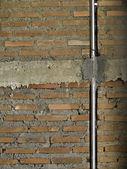 Ziegelmauer mit metallrohr. — Stockfoto