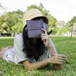 Woman laying on grass and thinking in park — Stock fotografie