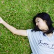 Young beautiful asian laying on the grass — Stock Photo #18169311