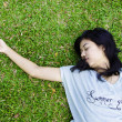 Young beautiful asilaying on grass — Stockfoto #18169311